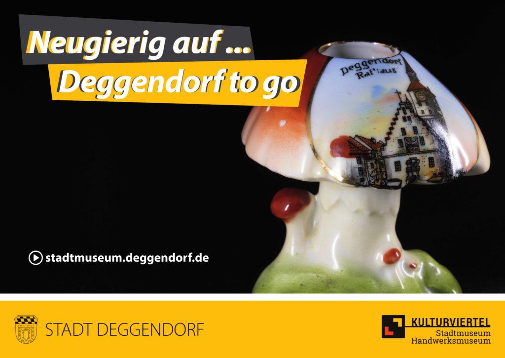 Neugierig auf: Deggendorf to go. Es ist ein Halter für einen Fingerhut in Form eines Pilzes mit einer Ansicht von Deggendorf zu sehen.