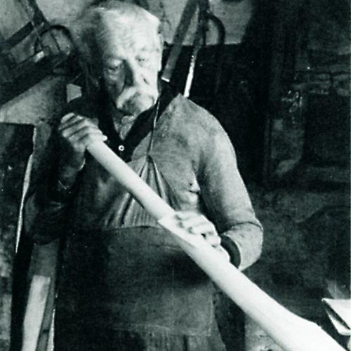 Historisches Bild eines Handwerkers, der ein längliches, rundes Holzstück schleift
