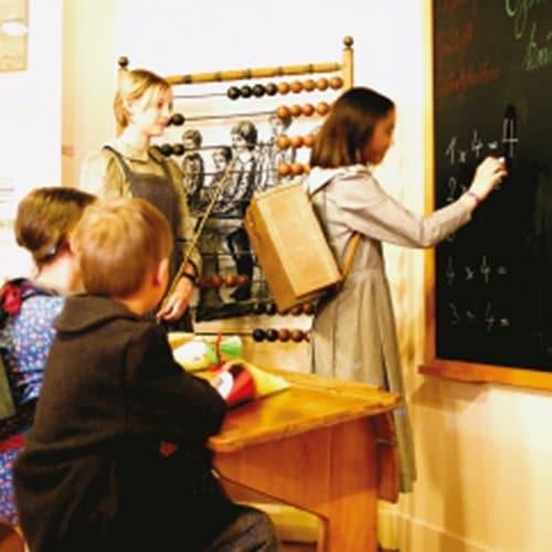 Kinder sitzen und stehen in einem historischen Klassenzimmer