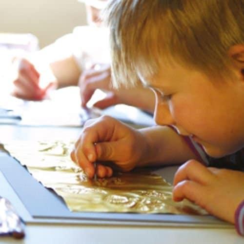 Kinder am stanzen eines goldfarbenen Blechs