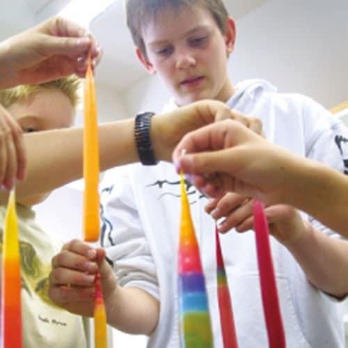 Kinder beim Wachsziehen einer Kerze