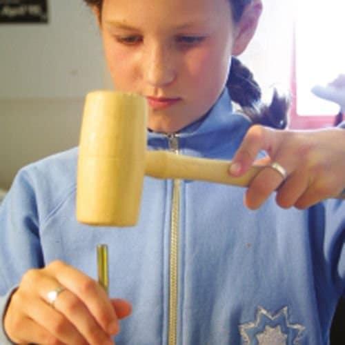 Kind schlägt mit einem Holzhammer auf einen Meisel