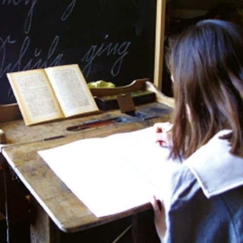 Kind schreibt mit Federkiel und Rußtinte