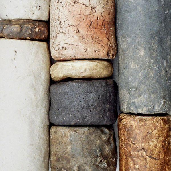 Aufeinandergelstapelte, verschieden-farbige Steine, die die gleiche Breite und Abrundung haben