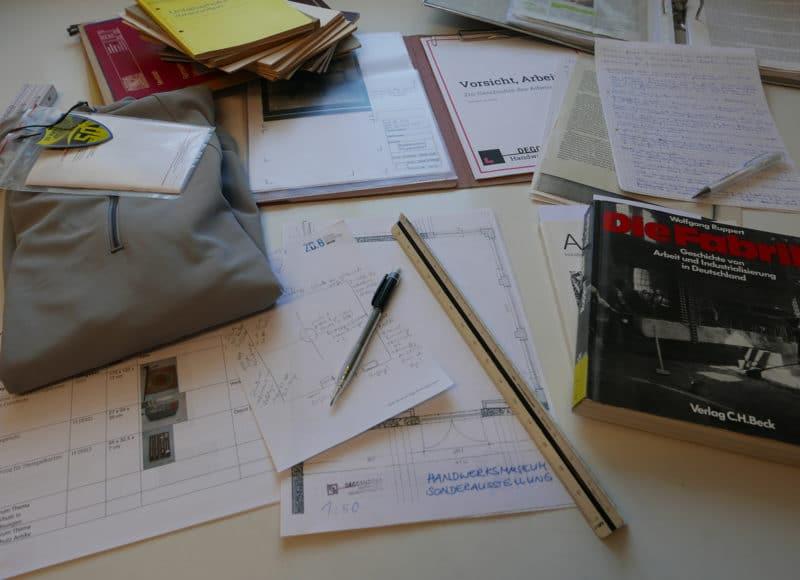 Schreibtisch voll mit Utensilien zur Vorbereitung einer Sonderausstellung
