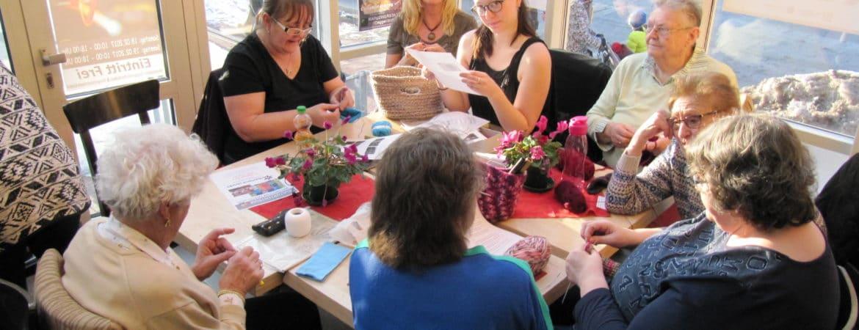 9 Menschen sitzen um einen Tisch im Handwerksmuseum Deggendorf bei der Veranstaltung Strickcafe beim gemeinsamen Stricken