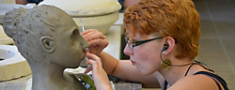 """Künstlerin der Keramikschule arbeitet an einem Ausstellungsstück von """"Zeitgeschichte"""" im Handwerksmuseum Deggendorf"""