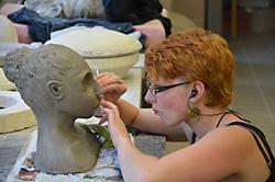 Künstlerin der Keramikschule arbeitet an einem Ausstellungsstück von